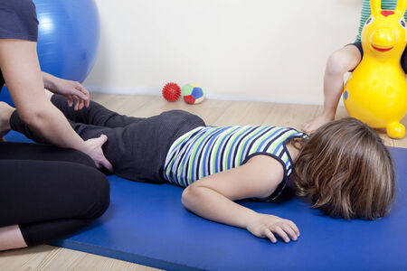 a female physiotherapist makes physiotherapy with young children Imagens