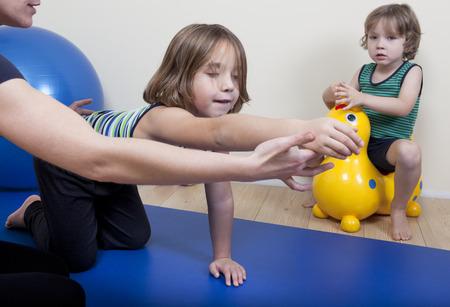 fisioterapia: un fisioterapeuta femenina hace que la fisioterapia con ni�os peque�os Foto de archivo