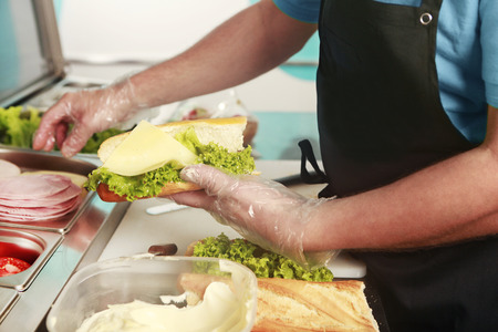 A cook making a fresh sandwich with different ingredients