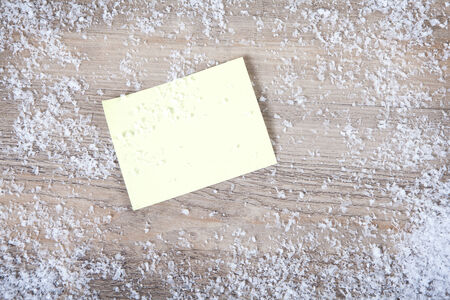 on a wooden background a yellow Sticky note with no text. Decorated with snow photo