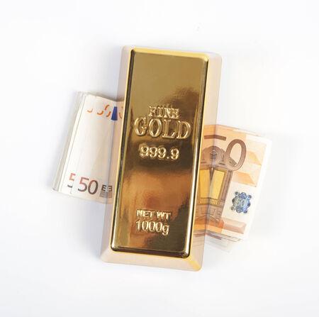 to seem: Gold bullion lies on a stack euro money seem