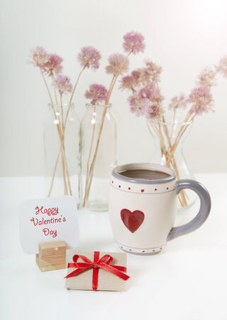 cordially: a sign with the text happy valentines day with a gift and a cup of coffee