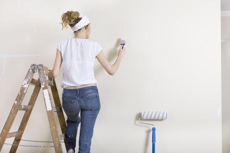Vrouw met penseel in de hand staande op een ladder en schilderen van een muur