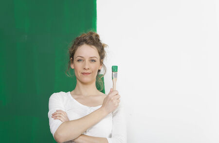 'face painting': young woman standing in front of a self painted wall with a brush Stock Photo