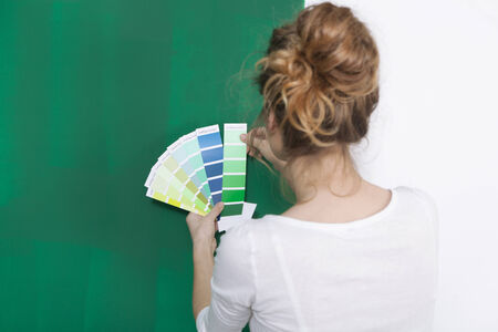 choosing selecting: young woman standing in front of a green painted wall and looks different colors