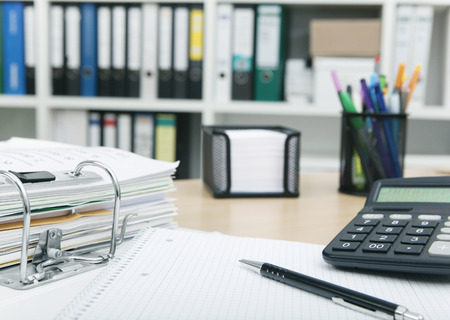 messily: Desk in an office with files and calculator Stock Photo