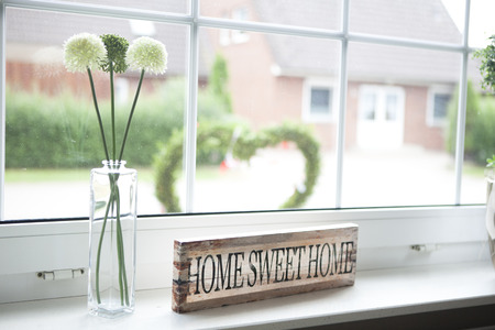 on a window sill in the house is a sign with the text home sweet home Foto de archivo