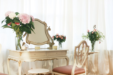 old dressing table decorated with flowers and chair