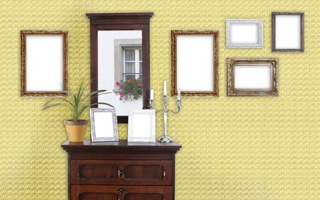 dresser: on a wall with a dresser hang several picture frames Stock Photo