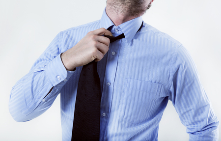 a businessman in shirt trying to solve the tie to get some air photo