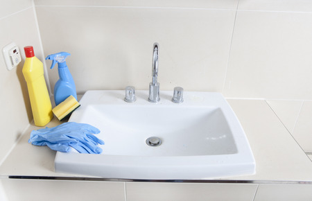 sanitizing: a dirty and calcified sink with cleaning gloves and cleaning products