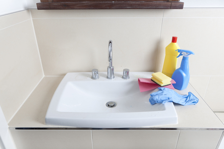 cleaning products: a dirty and calcified sink with cleaning gloves and cleaning products