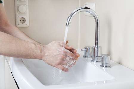 Wash hands with soap and water on a modern washstand