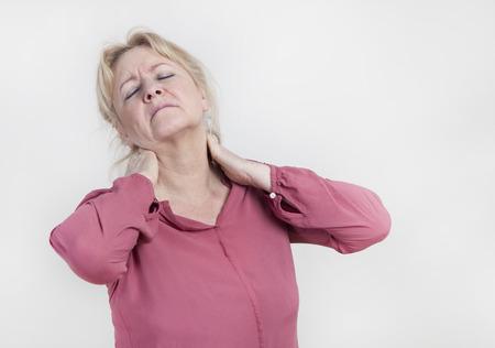 Una mujer rubia mayor celebración de su cuello con la mano Foto de archivo - 38760847