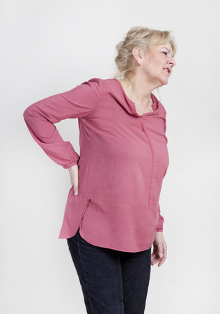 woman standing back: an older woman has pain and holds the back