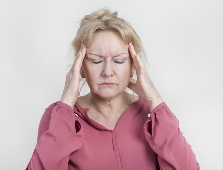 an older woman has pain and holds his head Imagens