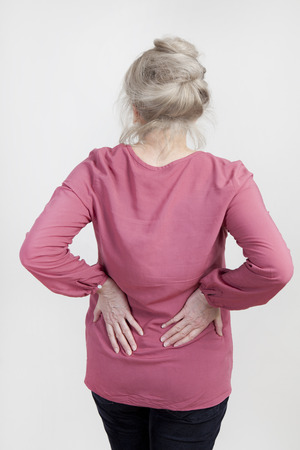 an older woman holds her back in pain