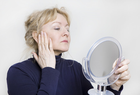an older woman looking in a hand mirror on her face