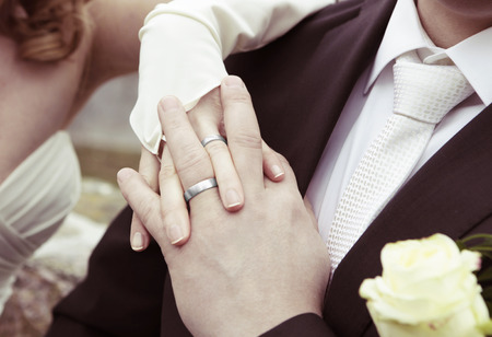 Bride and groom showing their silver wedding rings, no face