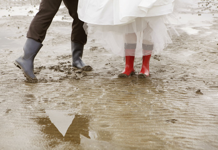 wadden: a married couple with rubber boots and wedding dress goes for a walk in the Wadden