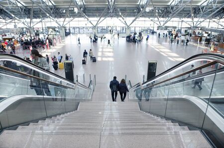 check in: Tourists with suitcases at Hamburg airport check in area