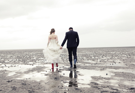Bride and groom go in rubber boots walk in the Wadden Sea