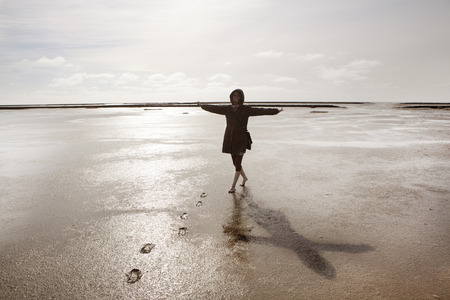 wadden: a holidaymaker walks in the Wadden Sea on the North Coast