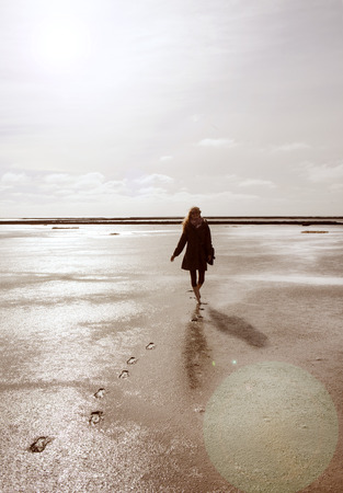 the wadden sea: a holidaymaker walks in the Wadden Sea on the North Coast