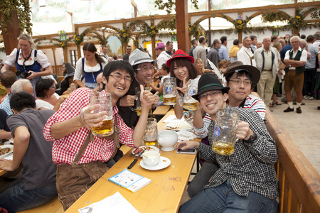 Japanese visitors to sit in the tent at the Oktoberfest and drink beer in a beer mug Sajtókép
