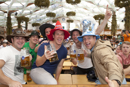 Visitors sit in the tent at the Oktoberfest and beer in a beer mug