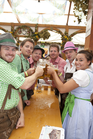 beerfest: Visitors sit in the tent at the Oktoberfest and drink beer in a beer mug