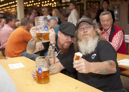 beerfest: Visitors sit in the beer tent at the Oktoberfest with a beer mug