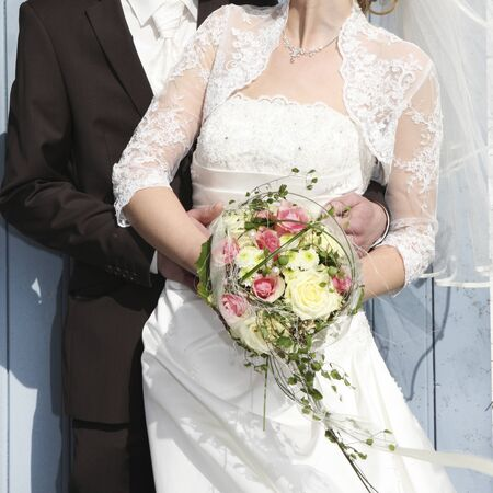 held: a bride in a white wedding dress with a bridal bouquet in her hand is held by her groom Stock Photo