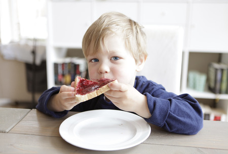 a blond boy sitting at a table and eating a jam sandwich Фото со стока