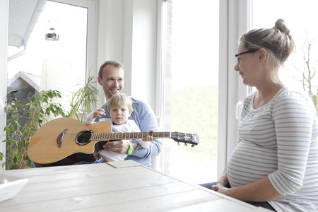 making music: a family sitting at the table, making music with the guitar