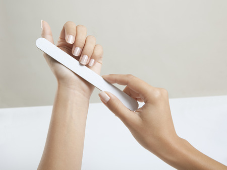 nail file: Perfect Woman hands with beautiful fingernails and a nail file Stock Photo