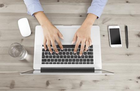 Vrouwelijke vingers te typen op een toetsenbord op een bureau, geen gezicht