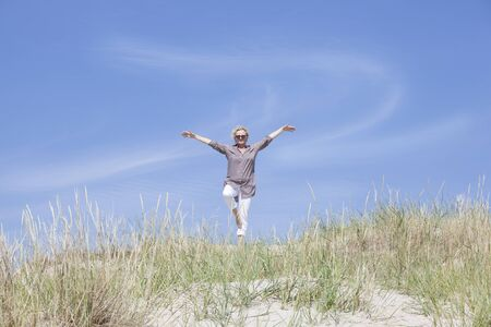 One Senior Woman does sports on the beach in the dunes