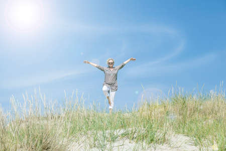 joga: One Senior Woman does sports on the beach in the dunes