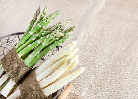 bundled: bundled fresh green and white asparagus in a basket with a cloth tape