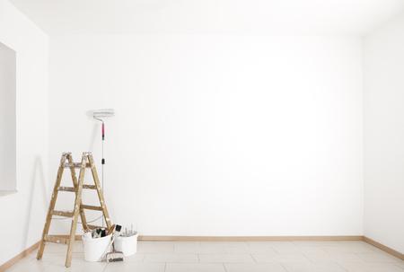 Leiter und Malerei Zubehör sind in einem leeren Raum