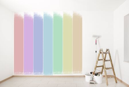 a choice of bright colors on a wall with ladder and painting tools Stock Photo