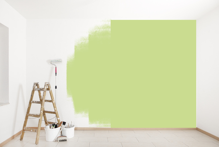 with green color is painted on a wall with ladder and painting tools