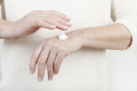 hand care: the hands of an elderly woman with hand cream