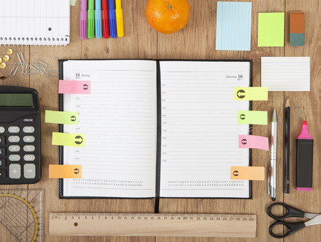 a calendar with Post it is situated on a desk with pencils and fruit