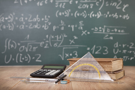 Schoolbooks and calculator lying on a wooden school desk in front of a green chalkboard with Mathematical formulas school Zdjęcie Seryjne