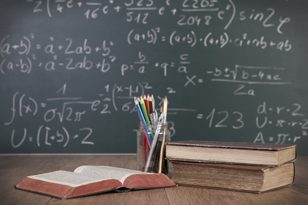 Schoolbooks and pencils lying on a wooden school desk in front of a green chalkboard with Mathematical formulas school