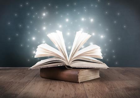libros antiguos: un viejo libro abierto sobre una mesa delante de una pizarra