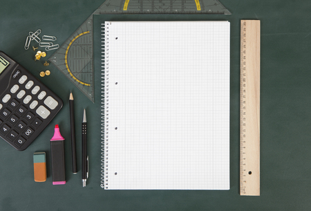 square background: a school board with notebook, ruler and set square, next to a calculator with pens Stock Photo