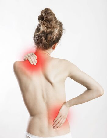exempted: a young woman holds her back in pain, white background and exempted